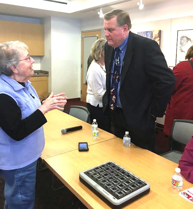 Mark Halliday, Assisted Living Services/Assisted Living Technologies Community Liaison, shares information with one of the attendees at the Shoreline Elder Care Alliance's aging at home seminar  at the Guilford Library.