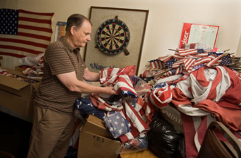 Tony Gianakos, American Legion Post 45 Commander, shows hundreds of tattered flags collected for the organization