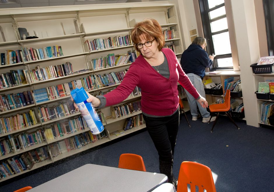 Teachers, Leni Grossomanides, left, and Heidi Boyd, right, work to disinfect the library at St. Joseph School in Meriden, Wednesday, February 1, 2017. St. Joseph School is closed for the remainder of the week after record high numbers of students fell ill within the past week. | Dave Zajac, Record-Journal