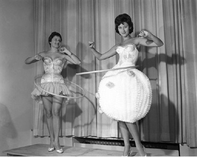Two models gracefully swing their new Hula-Hoops as they display the latest bodice creations in lingerie at a fashion show in Frankfurt, West Germany, Oct. 21, 1958. The slimming device has swept across America and is now catching on fast in Europe. (AP Photo/Riethausen)