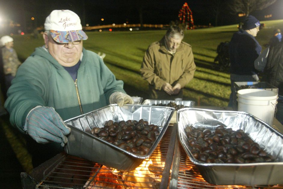 Peter Carusone, an employee of the Meriden Parks Department, roasts chestnuts over a fire during the Christmas festival in Hubbard Park on Dec. 12, 2006.