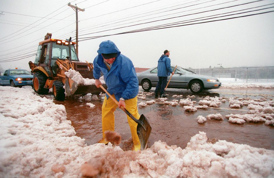 RJ file photo - Tom Gaj, from the Meriden Parks Department, clears a catch basin on Centennial Avenue near Platt High School Jan. 15, 1999. In the background in Pete Daniels, who also works for the department.