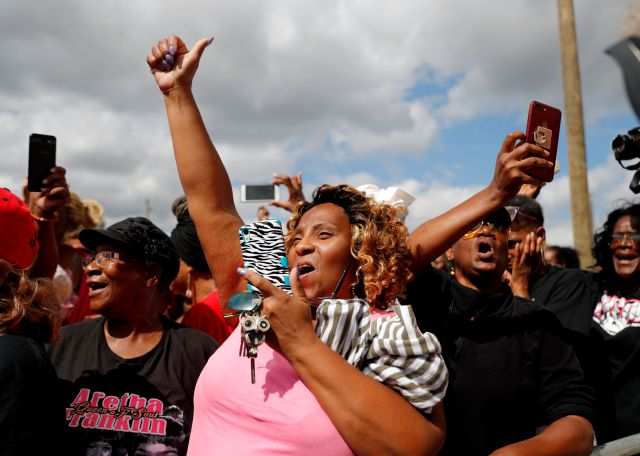 Sheila Williams, center, raises her arm and sings with others standing outside New Bethel Baptist Church as a viewing for Aretha Franklin is held inside, Thursday, Aug. 30, 2018, in Detroit. Franklin died Aug. 16, 2018 of pancreatic cancer at the age of 76. (AP Photo/Jeff Roberson)