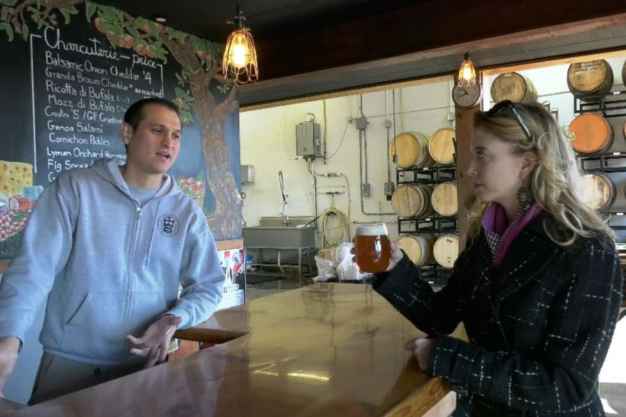 Record-Journal Digital Content Producer Ashley Kus, right, tries some Roasted Maple cider with  Miguel Galarraga, owner of New England Cider Company, on North Plains Industrial Road in Wallingford on Monday.