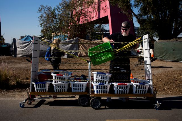 Joel Sheehan, who does free laundry for homeless people living on the Santa Ana River trail, delivers washed clothes in baskets, each labeled with an individual
