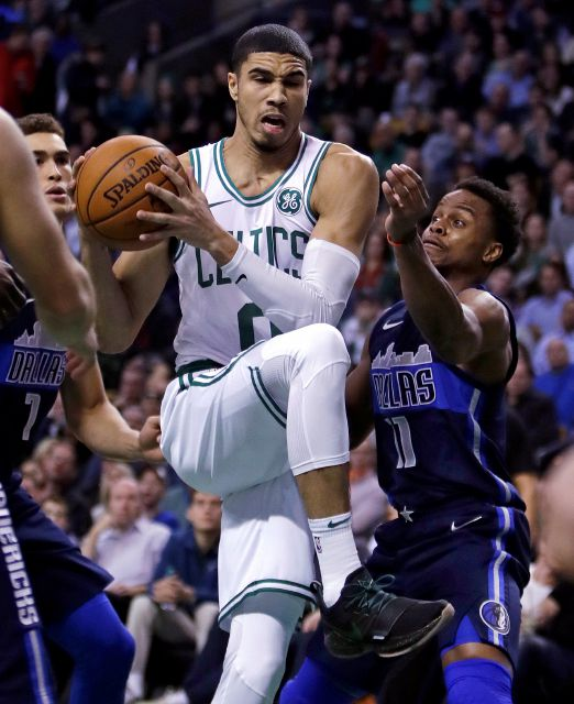 Boston Celtics forward Jayson Tatum, left, tries to drive past Dallas Mavericks guard Yogi Ferrell (11) during the first quarter of an NBA basketball game in Boston, Wednesday, Dec. 6, 2017. (AP Photo/Charles Krupa)