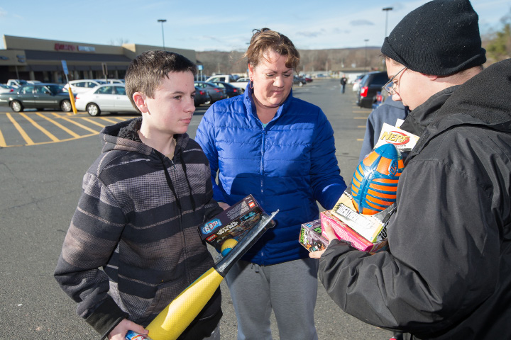 Braeden Laflamboise, 14, left, and his mom, Trisha, deliver toys to Sea Cadet Jayden Machowski, 14, Saturday during the annual Southington Police Department's Stuff a Cruiser at the Wal-Mart in Southington.| Photos by Justin Weekes, Special to the Record-Journal