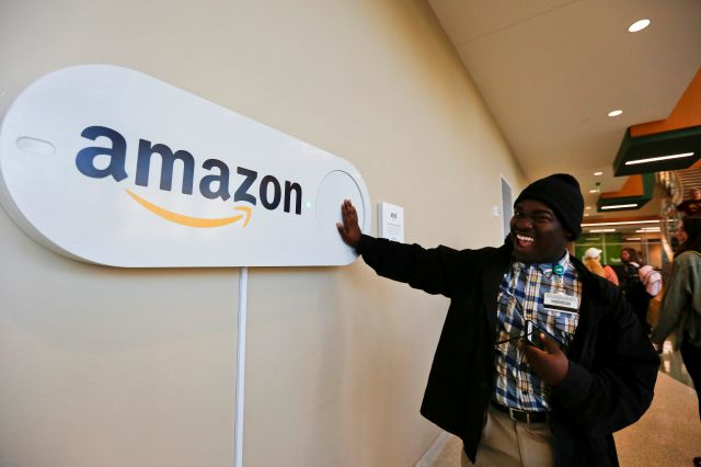 FILE - In this Monday, Oct. 16, 2017, file photo, Zavian Tate, a student at the University of Alabama at Birmingham, pushes a large Amazon Dash button, in Birmingham, Ala. The buttons are part of the city