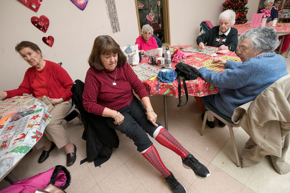 "Mary Bassett, of Meriden, shows off her ""Kinky Boots"" socks (fashioned after the Broadway play) during a bingo game on Valentine"