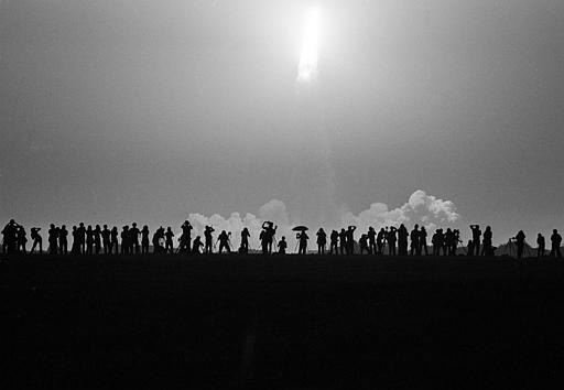 A line of photographers are silhouetted as the Space Shuttle Challenger lifts off Pad 39A early Aug. 30, 1983, at the Kennedy Space Center. (AP Photo/Phil Sandlin)