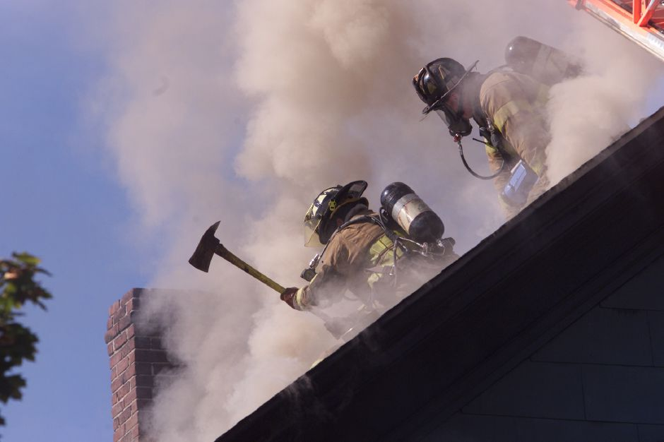 Meriden firefighters break through the roof to vent a house fire on Cottage Street in Meriden Thursday afternoon October 24, 2002.