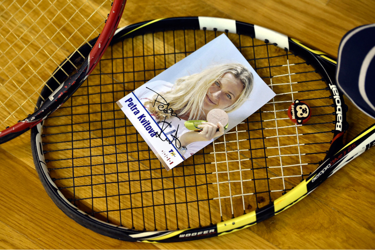 A photograph of Czech tennis player Petra Kvitova lies on a tennis racket during a charity tennis exhibition in Brno, Tuesday, Dec. 20, 2016. Two-time Wimbledon champion Kvitova had to cancel the event because she has been injured during an attack in her flat in the Czech Republic. Kvitova's spokesman Karel Tejkal said Tuesday Dec. 20, 2016. She suffered a left hand injury and has been treated by doctors. (Vaclav Salek/CTK via AP) SLOVAKIA OUT