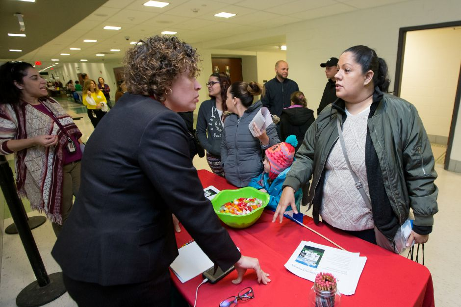 Johanna Roman speaks with Betran Roman of Casa Boricua Wednesday during a welcome dinner and orientation for Puerto Rican students and families at Maloney High School in Meriden December 13, 2017 | Justin Weekes / For the Record-Journal