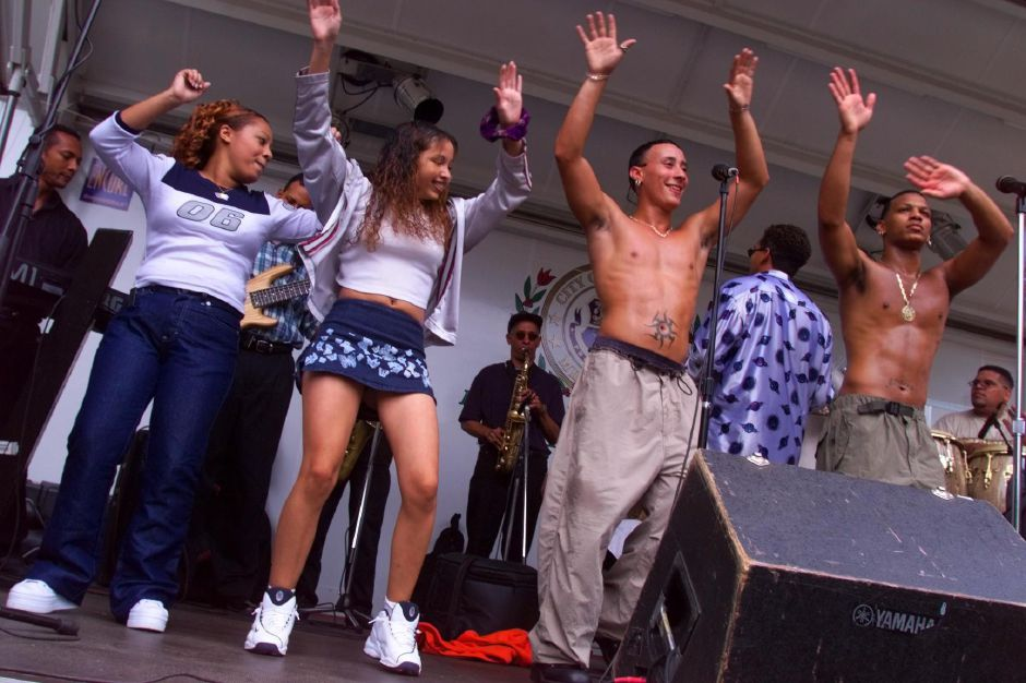Audience participants Melissa Cordero,16 (far left) and Vanessa DeJesus,13- both of Meriden get in sync on stage with Tumba Banda members Favio Acevedo of Ynkers, NY and Eddie Calderon of New Britain during their musical performance at the Puerto Rican Festival at Hubbard Park on Sunday Aug. 22, 1999.