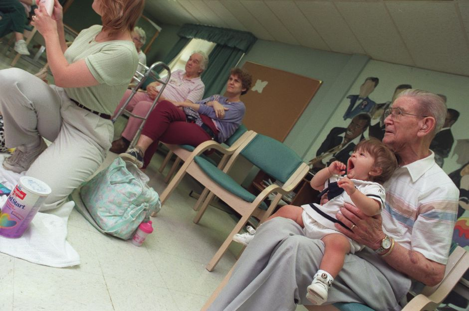 RJ file photo - At the Brook Hollow Health Care Center in Wallingford, 10 month old Teresa Maria Cosentino yawns while sitting on the lap of resident Robert Jenkins, 87, during the baby