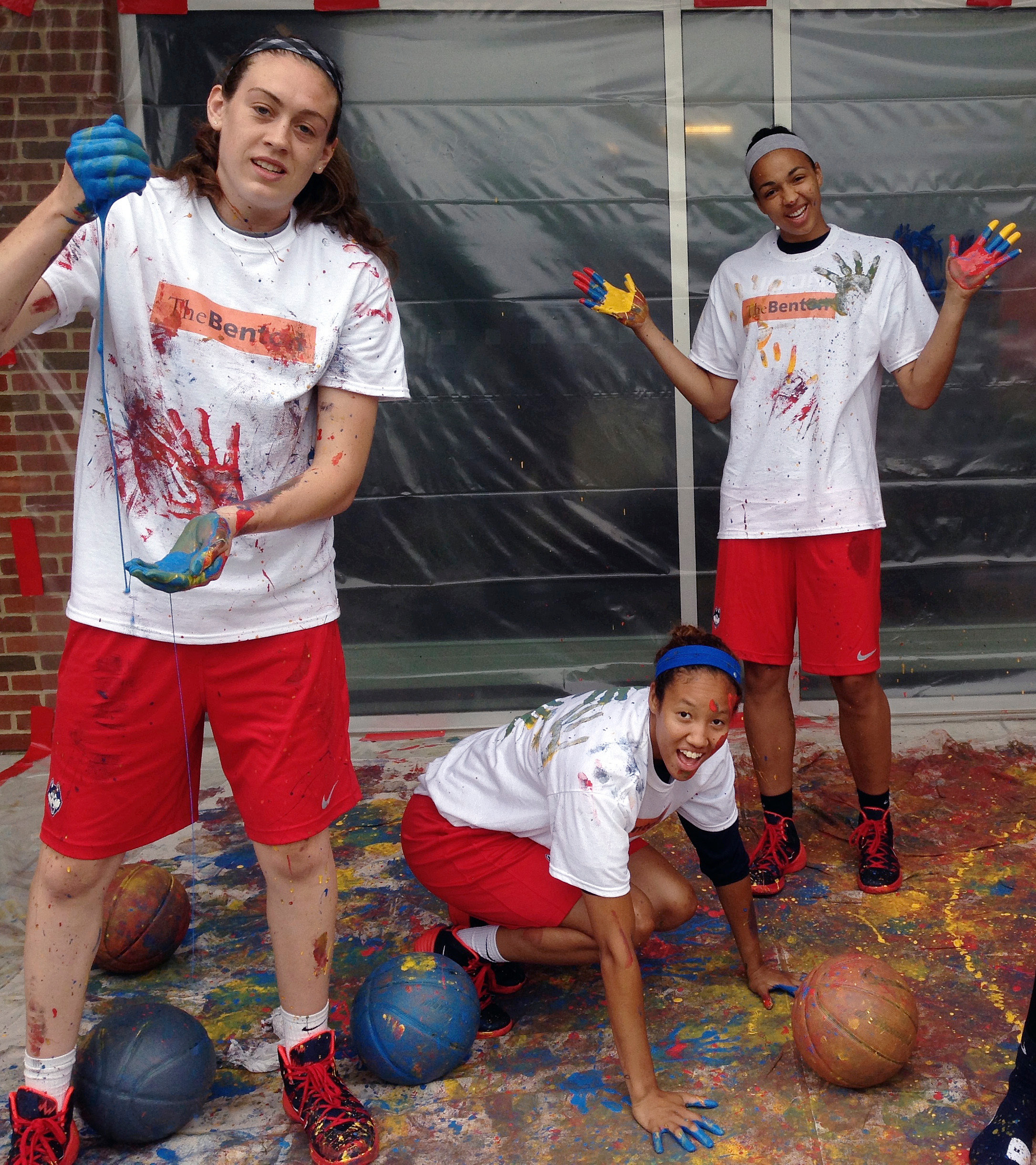 In this June 12, 2014 photo released by the University of Connecticut, UConn women basketball players Breanna Stewart, left, Saniya Chong, kneeling, and Kiah Stokes, right, pose after dribbling paint-covered basketballs on a canvas to create a painting on campus in Storrs, Conn. The schools William Benton Museum of Art will open an exhibit on Jan. 23, 2015, titled In the Paint: Basketball in Contemporary Art, which will feature 22 basketball-related paintings, photographs and sculptures, including this painting.  (AP Photo/University of Connecticut, Kevin DeMille)