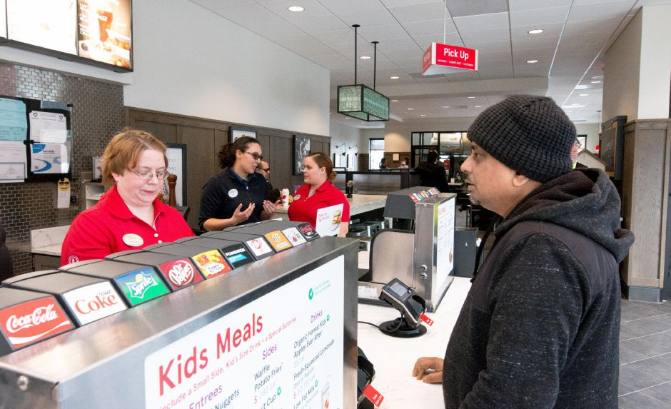 Shaikh Faruk, of Southington, orders a meal from Anita Bryant on the opening day of the Southington Chick-Fil-A on Thursday. | Devin Leith-Yessian/Record-Journal