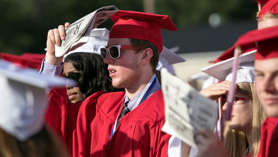 Graduate Matthew Nugent shades his shades from the sun during graduation ceremonies at Cheshire High School, Wednesday, June 14, 2017. | Dave Zajac, Record-Journal