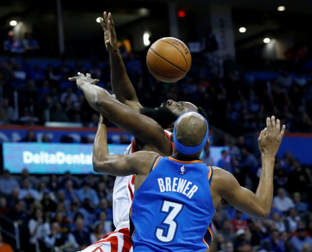 Houston Rockets guard James Harden, rear, loses the ball after a foul by Oklahoma City Thunder forward Corey Brewer (3) in the first half of an NBA basketball game in Oklahoma City, Tuesday, March 6, 2018. (AP Photo/Sue Ogrocki)