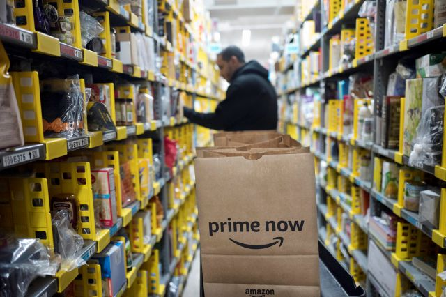 A clerk reaches  for an item for a customer order at the Amazon Prime warehouse in New York in December. File photo, Associated Press
