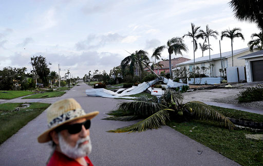 A fallen palm tree and a roof litters a street as Rick Freedman checks his neighborhood