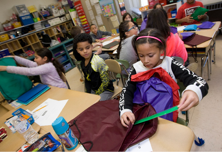 Aysha Mena, 9, adds school supplies to backpacks Tuesday with her third-grade class at Roger Sherman School in Meriden. | Dave Zajac, Record-Journal
