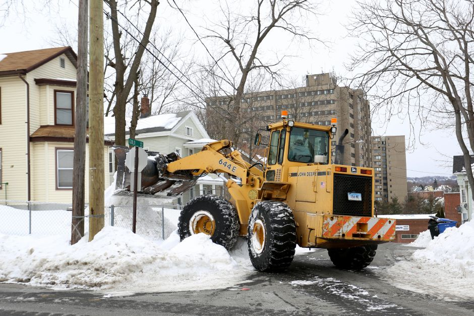 A city payloader dumps snow from Crown Street in the yard of a nearby home while clearing Meriden streets Friday Feb. 6, 2015. | Richie Rathsack/Record-Journal