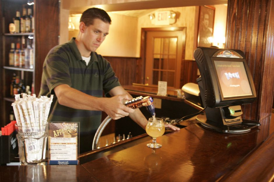 Co-owner Dan Sugrue prepares a drink for a customer at the bar of Brannigan