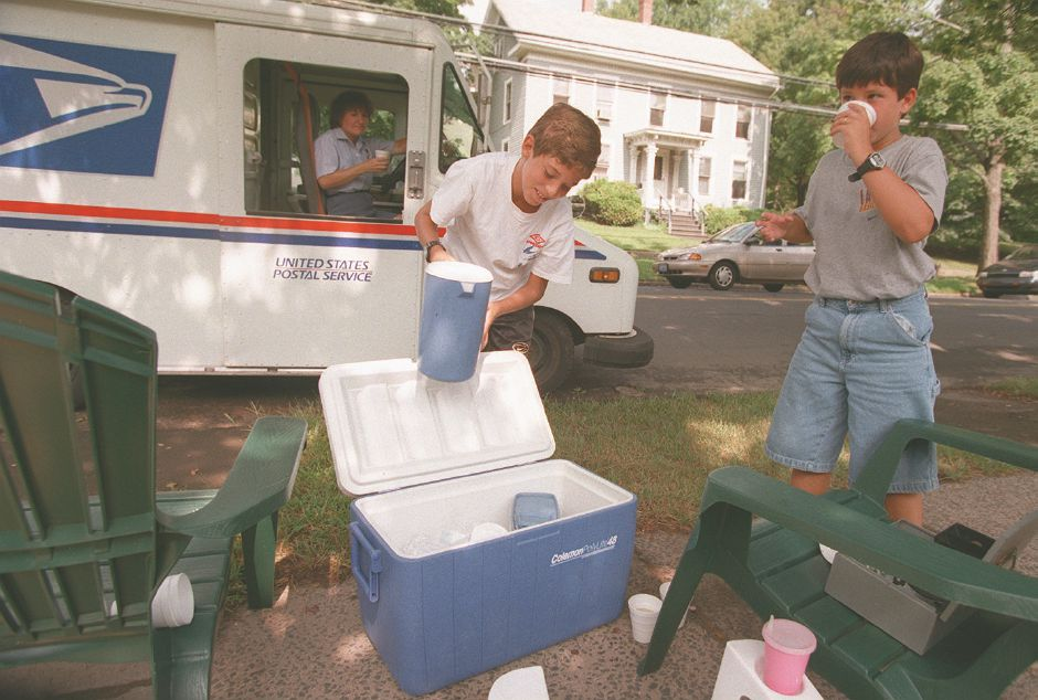 RJ file photo - Juan Figlewski, 11, left, and his brother Raymond, 9, sell lemonade to letter carrier Karen Tyler in front of their South Elm Street home in Wallingford Aug. 18, 1998.