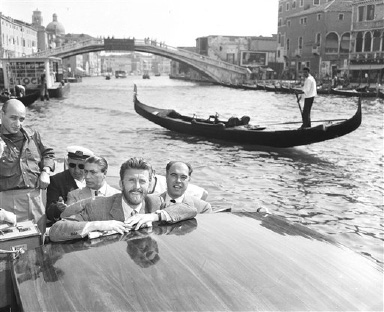 Actor Kirk Douglas, with beard, on a motorlaunch in Venice after arrival by rail from Rome, Aug. 30, 1953. Kirk Douglas arrived for the showing of Hollywood