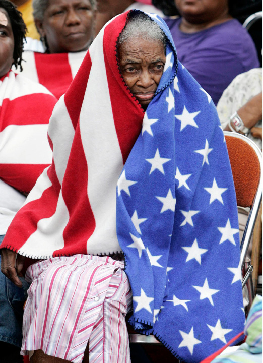 FILE - In this Thursday, Sept. 1, 2005 picture, Milvertha Hendricks, 84, covered with a blanket depicting a U.S. flag, waits in the rain with other flood victims outside the convention center in New Orleans. (AP Photo/Eric Gay)
