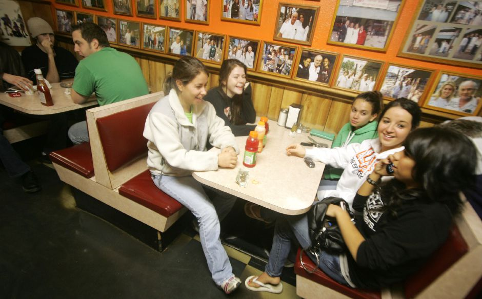 Seated together in a booth is Kelly Kennedy, far left and Erika Zyskowski, right. Across from them are Kim Kennedy, left, Erica Cassello, middle, and Mercedes Otano, right. This is at Tom
