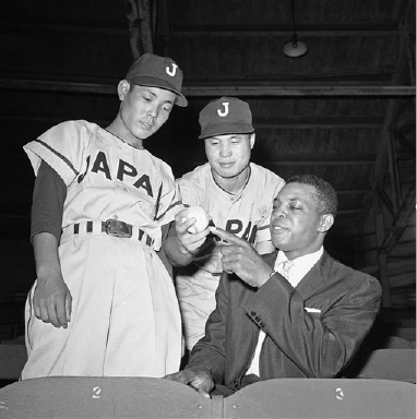 Willie Mays, right, San Francisco Giants' outfielder, gets some pointers on the Japanese screw-ball from Tetsuo Kaneko, center, star pitcher for the Japan High School All-Star team during their game with the Los Angeles Dodgers' Rookie team at Wrigley Field, August 29, 1959, Los Angeles, Calif. Keneko, 17, is from Saijo High School. At left is Yukio Minegishi, 18, from Toohoku High School and star outfielder of the team. The Japanese team won the game 1 to 0. (AP Photo/Don Brinn)