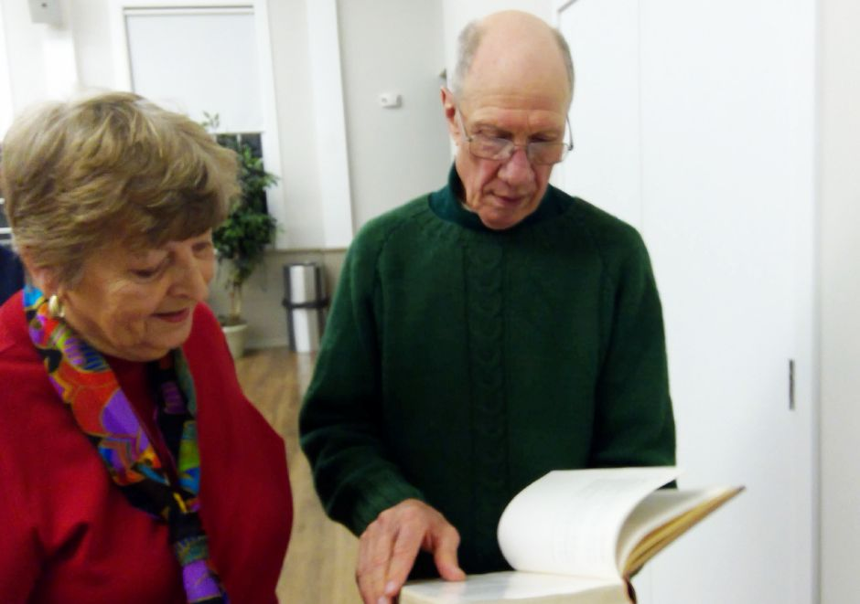 Leah Sanders and Dr. Bob Giddings look over books together after his recent First Congregational Church presentation on avian life.