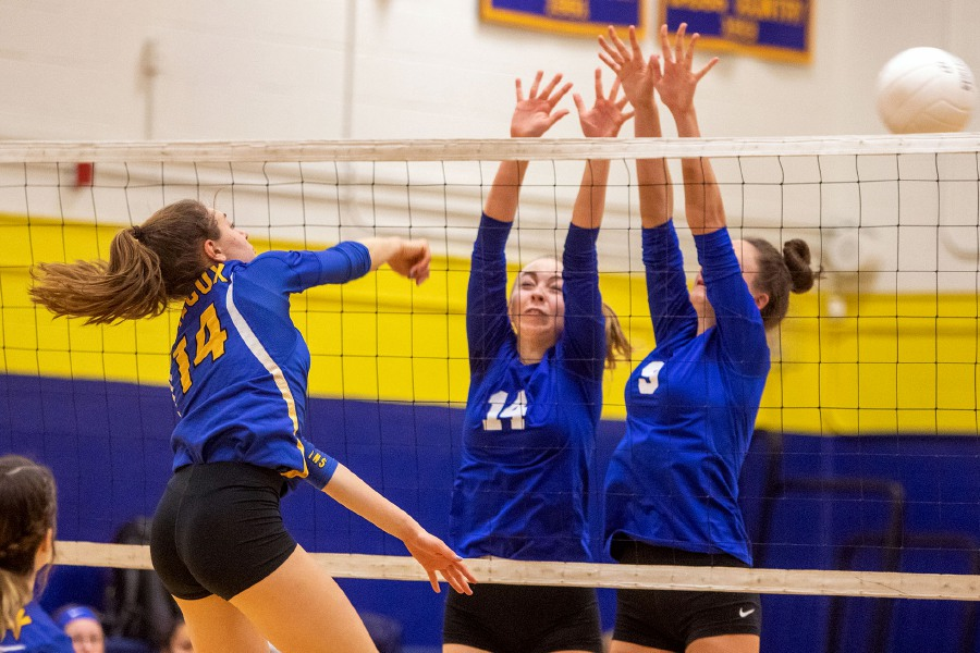 Wilcox Tech's Chloe LaBissoniere drives a ball past the attempted block of Bacon Academy's Claire Galarneau, left, and Julia Baehr during the second set of Wednesday's second-round Class M state volleyball match in Meriden. LaBissoniere finished with seven kills.  Aaron Flaum, Record-Journal