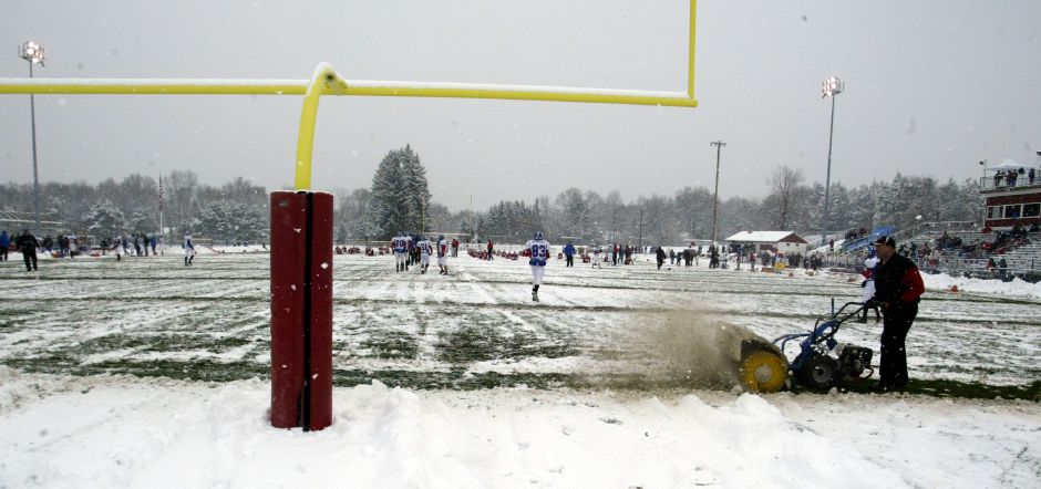 Bob Bartone uses a machine to brush the snow off the endline at Cheshire H.S. during warmups before the Cheshire versus Southington game on Nov. 25, 2005. About four inches of snow fell on the field overnight.