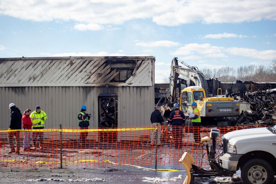 Investigators talk while looking through the debris March 4, 2019 after a fire tore through Tops Marketplace in Southington. | Richie Rathsack, Record-Journal