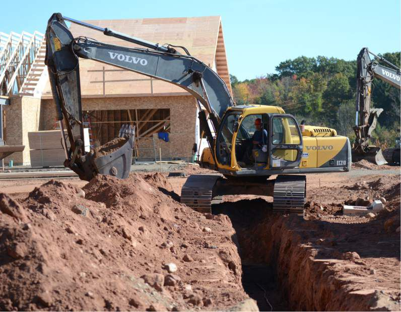 An excavator digs a trench at 1095 West St., Southington, on Friday, Oct. 20, 2017. | Bryan Lipiner, Record-Journal