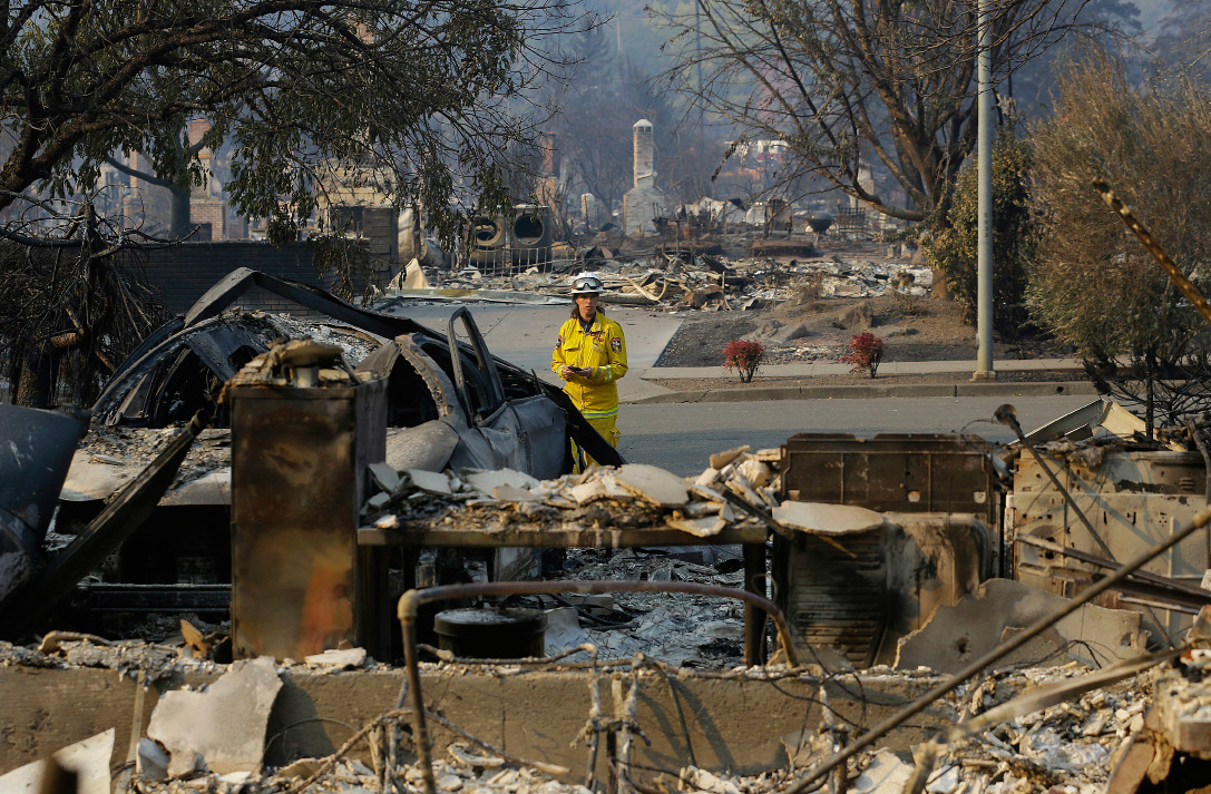 Cal Fire forester Kim Sone inspects damage at homes destroyed by fires in Santa Rosa, Calif., Thursday, Oct. 12, 2017. Gusting winds and dry air forecast for Thursday could drive the next wave of devastating wildfires that are already well on their way to becoming the deadliest and most destructive in California history. (AP Photo/Jeff Chiu)