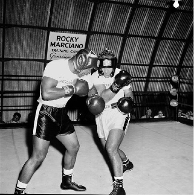 World heavyweight champion Rocky Marciano, right, charges into his sparring partner, Toxie Hall, during workout at his Grossinger, N.Y., training camp, Aug. 31, 1955. Rocky
