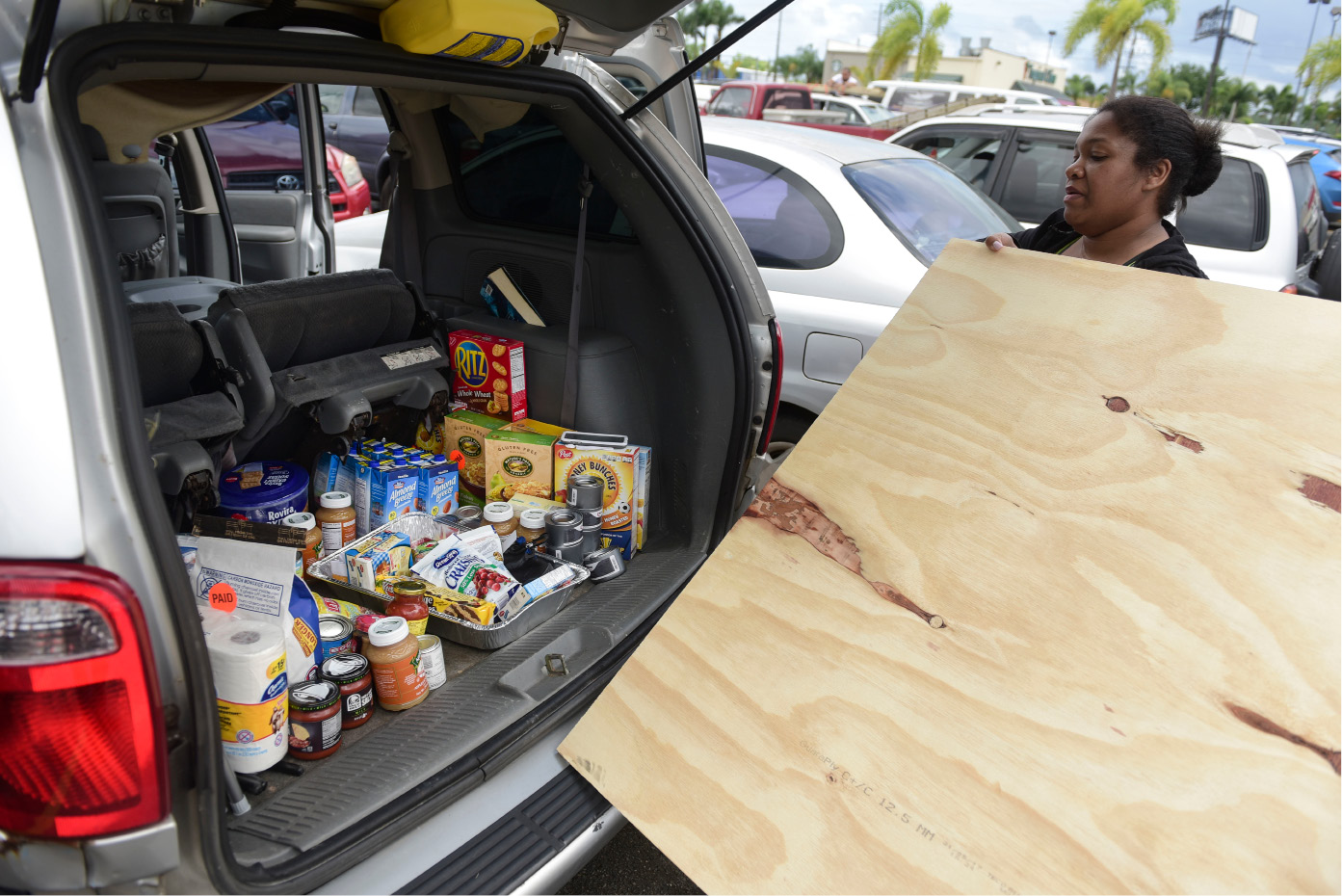 After loading the back of her vehicle with food Maria Minier loads a recently purchased wood panel to be used in preparation for Hurricane Irma, in Carolina, Puerto Rico, Tuesday, Sept. 5, 2017. Irma grew into a dangerous Category 5 storm, the most powerful seen in the Atlantic in over a decade, and roared toward islands in the northeast Caribbean Tuesday. (AP Photo/Carlos Giusti)