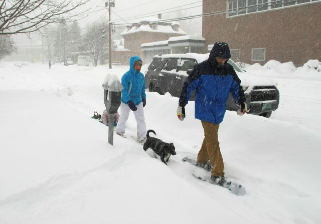 Will Roberts and his wife Julia Chafets snowshoe in downtown Montpelier, Vt., during a snowstorm on Sunday, Jan. 20, 2019. Chafets is pulling a sled carrying their daughter. (AP Photo/Lisa Rathke)
