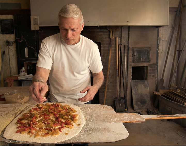 Longtime pizza maker Paul Bernier prepares an eggplant, pepper and garlic pie at The Little Rendezvous pizza restaurant on Pratt Street in Meriden, Wednesday, March 22, 2017. Bernier will work his final shift at the pizzeria this weekend. | Dave Zajac, Record-Journal
