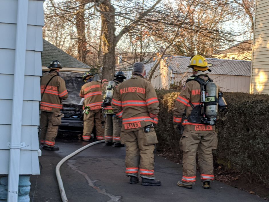 Firefighters extinguish a vehicle fire at 289 South Cherry St. Wednesday afternoon. The call initially came in as a possible structure fire in the residence where the car was parked. No injuries were reported, although the vehicle was totalled. |Mike Gagne, Record-Journal