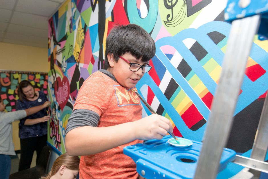 Sebastian Pinos, 12, gets some paint while working on a mural being painted at the Ulbrich Boy