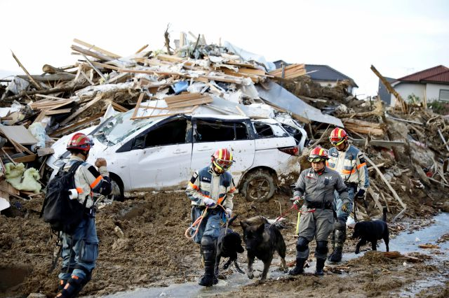 Firefighters with rescue dogs search for missing people after heavy rain hit southwestern Japan, in Kumano town, Hiroshima prefecture, Monday, July 9, 2018. Rescuers in southwestern Japan dug up more bodies Monday as they searched for dozens still missing after heavy rains caused severe flooding and left residents to return to their homes unsure where to start the cleanup. (Kyodo News via AP)
