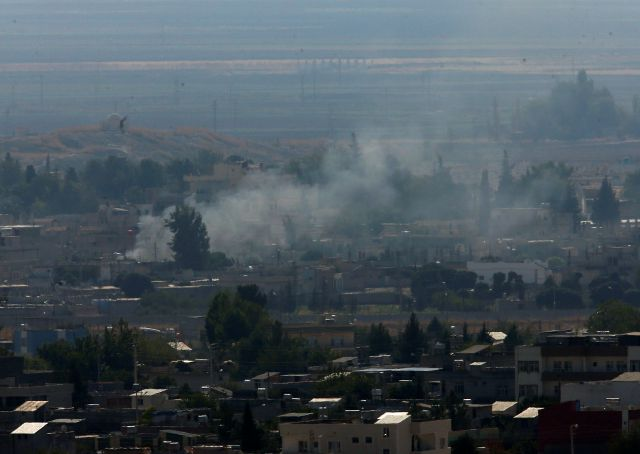 In this photo taken from the Turkish side of the border between Turkey and Syria, in Ceylanpinar, Sanliurfa province, southeastern Turkey, smoke billows from targets in Ras al-Ayn, Syria, caused by shelling by Turkish forces, Friday, Oct. 18, 2019. Fighting continued in a northeast Syrian border town at the center of the fight between Turkey and Kurdish forces early Friday, despite a U.S.-brokered cease-fire that went into effect overnight. Shelling and gunfire could be heard in and...