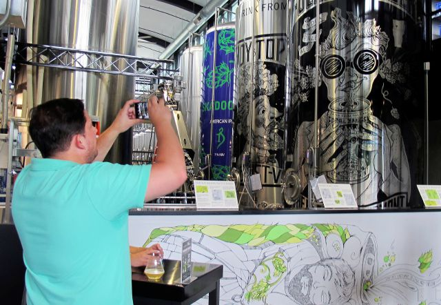In this Aug. 1, 2018 photo, Walter Richter, of New York City, makes a photograph during a visit to the Alchemist brewery in Stowe, Vt. The woods of northern New England are luring beer tourists. No discussion of beer in Vermont is complete without The Alchemist, a family run brewery that specializes in fresh, unfiltered IPA. (AP Photo/Wilson Ring)