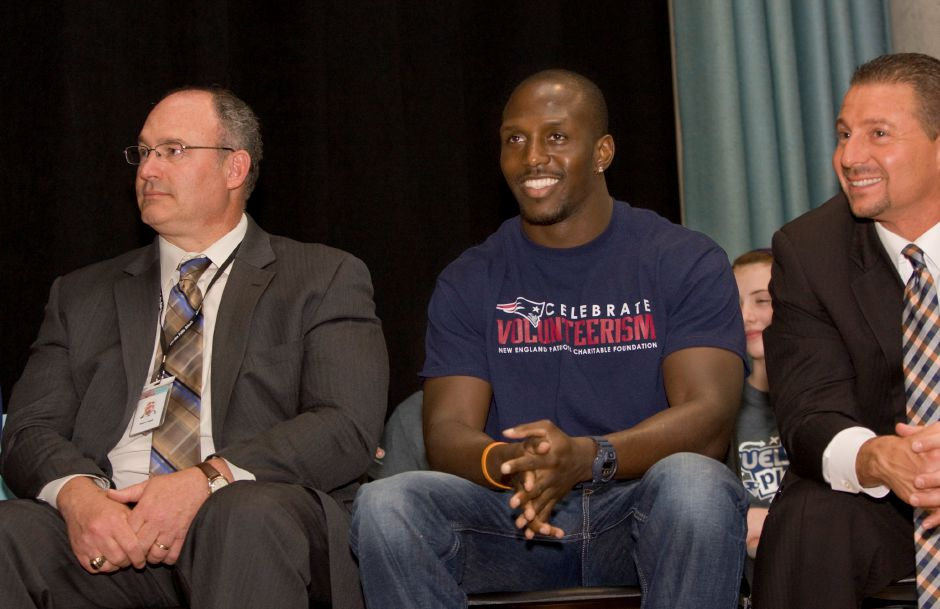 New England Patriots safety and Super Bowl champion Devin McCourty smiles between Robert Angeli, associate school superintendent, left, and Mark D. Benigni, school superintendent, right, during a visit promoting health and nutrition at Washington Middle School in Meriden, Wednesday, April 29, 2015. | Dave Zajac / Record-Journal