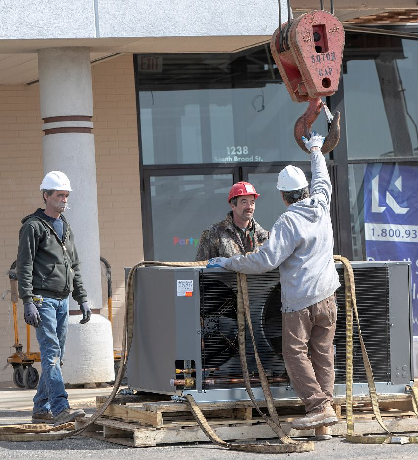 Workers prepare to attach a crane hook to an air conditioning unit as construction continues at Aldi in Wallingford, Wed., Mar. 27, 2019. Dave Zajac, Record Journal